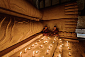 Asian monks lighting candles in temple, Myanmar