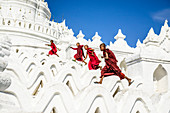 Asian monks running on white temple walls, Hsinbyume Pagoda, Mandalay, Sagaing, Myanmar