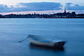 Motion blur, in calm water, a city skyline in the distance, with tall buildings and lights, Denmark