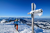 Man and woman on ski tour go by snowy summit cross over, Hochries, Chiemgau Alps, Bavaria, Germany