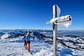 Mann und Frau auf Skitour gehen an verschneitem Gipfelkreuz vorbei, Hochries, Chiemgauer Alpen, Bayern, Deutschland