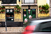 Facade of a pub with passing car in Lisbon, Portugal