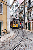 Yellow tram in narrow street, Alfama, Lisbon, Portugal