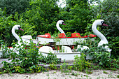Overgrown swan-shaped boats in the abandoned amusement park in the Plänterwald, Treptow, Berlin, Germany