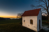 Small chapel next to a large tree in backlight in the evening. Seehausen, Starberger See, Bavaria, Germany