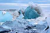 A wave breaking on the icebergs on Black Diamond Beach in southeast Iceland, Breidamerkursandur, Iceland, Europe