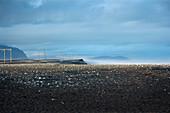 Blick auf Strommasten neben der Ringstrasse, im Vordergrund schwarzer Vulkansandstrand im Südosten Islands, Europa