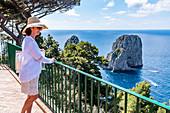 Young Italian woman at the observation deck of the Faraglioni rocks on Capri, Capri Island, Gulf of Naples, Italy