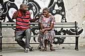 2 friends are chatting and laughing on a street bench in the capital of Cuba. Havana