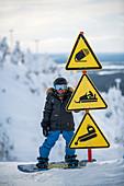 Kleiner Junge auf seinem Snowboard neben Warnschildern, Winter in Finnland