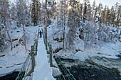 Kleiner Junge stapft mit Schneeschuhen über eine Brücke, Winterwald, Finnland