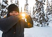 Kleiner Junge hält die Sonne in seinen Händen, Winter in Finnland