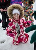 Kleinkind im Schneeanzug bewundert geangelten Fisch, Eisfischen in Finnland