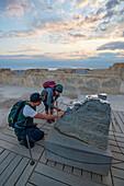 Zwei Wanderer unterwegs im Nationalpark Masada, betrachten ein Modell der Festung Masada, Israel