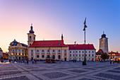 Piata Mare with Roman Catholic parish church, town hall and town hall tower at sunset, Sibiu, Transylvania, Romania