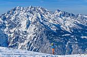 Frau auf Skitour steigt auf, Watzmann im Hintergrund, Kleine Reibn, Schneibstein, Berchtesgadener Alpen, Nationalpark Berchtesgaden, Berchtesgaden, Oberbayern, Bayern, Deutschland