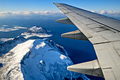 Airplane wing with snowy mountains, aerial view, near Bodö, Nordland, Norway