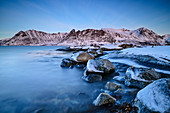 Icy rocks in sea bay with snowy mountains, Lofoten, Nordland, Norway
