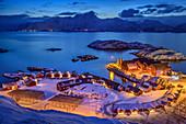 Illuminated port of Mortsund with Norwegian red fishermen's houses, Mortsund, Lofoten, Nordland, Norway