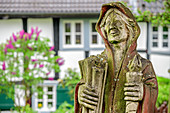 Wooden figure stands in front of half-timbered house, Blankenberg, natural area Sieg, Bergisches Hochland, North Rhine-Westphalia, Germany