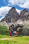 Advertising board of the Val Gardena with woman and man in traditional costume, Sassolungo in the background, Sellapass, Val Gardena, Dolomites, UNESCO World Heritage Dolomites, South Tyrol, Italy