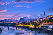 Beleuchtete Altstadt von Belluno über dem Fluss Piave mit Schiara-Gruppe im Hintergrund, Belluno, Dolomiten, UNESCO Welterbe Dolomiten, Venetien, Italien