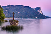 Rock with cross in the Mondsee at dawn, Drachenwand in the background, Mondsee, Salzkammergut, Salzburg, Austria