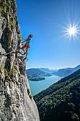 Frau begeht Klettersteig an Drachenwand, Mondsee im Hintergrund, Drachenwand, Mondsee, Salzkammergut, Salzburg, Österreich