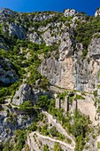 France, Herault, Saint Guilhem Le Desert, Max Negre's cliffs into the Cirque de l'Infernet, walkers on the Via Tolosana on the Route of Compostela, the passage of Fenestrelles fitted out formerly by the monks of the abbey to cross this rocky bolt
