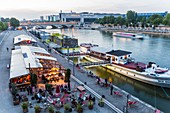 France, Paris, area listed as World Heritage by UNESCO, the banks of the Seine Quai Francois Mauriac, restaurants and barges on the Seine
