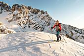 Skitourengeherin steigt in der felsigen Kulisse des Wilden Kaisers im Morgenlicht auf, Gruttenhütte, Tirol, Österreich