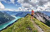 Trailläuferin läuft auf Bergrücken zwischen Seekarspitze und Seebergspitze am Achensee, Tirol, Österreich