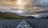 Dramatische Wolkenstimmung über einsamer Straße in den Westfjorden, Island