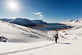 Skitourengeherin im Aufstieg bei bestem Wetter, Westjorde, Island