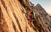 Junge Bergsteigerin steigt im Abendlicht durch felsige Flanke, Scheffauer, Wilder Kaiser, Tirol, Österreich