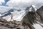 Trailrunner springt in hochalpiner Landschaft auf einem Grat, Schönbichler Horn, Schlegeis, Zillertaler Alpen, Tirol, Österreich