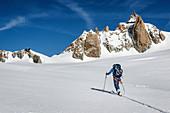 Skitourengeherin im Aufstieg durch das Vallée Blanche mit der Aguille de Cosmiques im Hintergrund, Chamonix, Haute-Savoie, Frankreich