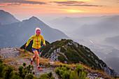 Trailrunner bei Sonnenaufgang am Gipfel des Bärenkopf hoch über dem Inntal, Achensee, Tirol, Österreich
