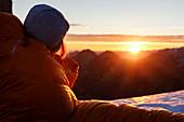 Woman in down sleeping bag looks at the rising morning sun, Gramai, Karwendel, Tyrol, Austria
