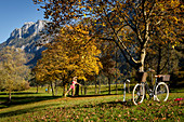 Young woman on a slackline stretched between autumn colored trees, Kiefersfelden, Bavaria, Germany