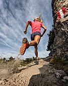 Trailrunner whirls dust on a sandy path, Bärenkopf, Achensee, Tyrol, Austria