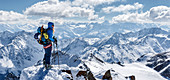 Mountaineer at the summit enjoys view of wintry Ötztal mountains, Tyrol, Austria