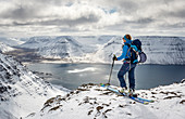 Ski tourer enjoys the view from Hólsfjall on the fjrod landscape of the Westfjords, Iceland