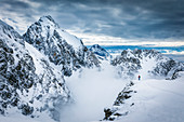 Ski tourers stand on a ledge in the Mieminger chain against a majestic mountain backdrop with a mystical cloud atmosphere, Tyrol, Austria