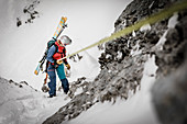 Ski alpinist rappels from back to back through rocky terrain, Mieminger chain, Tyrol, Austria