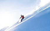 Skitourengeherin fährt im Gegenlicht der tiefstehenden Sonne durch einen unberührten Pulverhang, Kitzbüheler Alpen, Tirol, Österreich