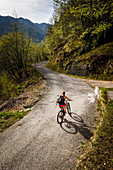Young woman rides a mountain bike up a narrow asphalt road, Lake Idro, Italy