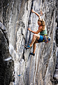 Young blonde woman climbs in the lead in an overhanging granite wall, Maltatal, Carinthia, Austria