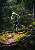 In bad weather, mountain biker jumps with an Enduro e-bike over a small hill, Kitzbüheler Alpen, Tyrol, Austria