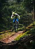 Mountainbiker springt bei schlechtem Wetter mit einem Enduro E-Bike über eine kleine Geländekuppe, Kitzbüheler Alpen, Tirol, Österreich